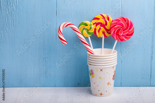 cups and lollipop on the blue wooden background - 79300692