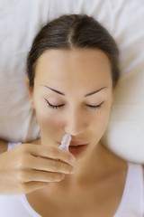 Sick young woman using nasal spray and laying on sofa