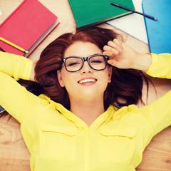 smiling student in eyeglasses lying on floor