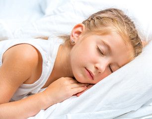 little girl sleeping in white bed