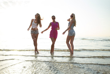 happy female friends dancing on beach