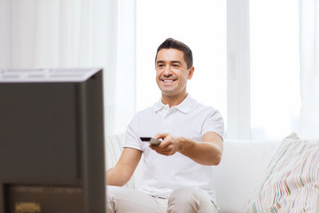 smiling man with remote control watching tv