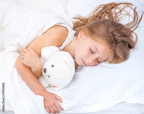 little girl  in the  bed with teddy bear - 79304662
