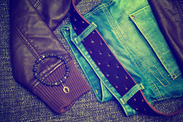 jeans with a leather belt, leather jacket, bracelet on the arm