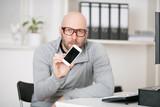 Mann am Arbeitsplatz mit Handy