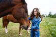 Young beautiful girl feeding a horse - 79306236