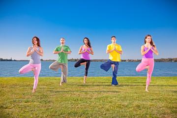 Young people practice Yoga asana on lakeside.