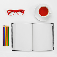 colored pencils, blank notebook, eyeglasses and cup of tea on a