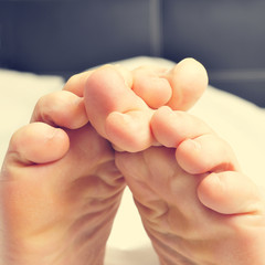 young man rubbing his bare feet together in bed