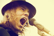 Man with long hair and hat shouting to microphone. Vintage music