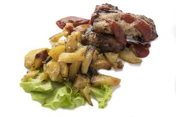 Fried potatoes with pork ribs on a salad leaf.