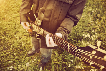 Young man playing on the guitar outdoors. Vintage, music