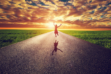 Happy woman jumping on long straight road, way towards sun