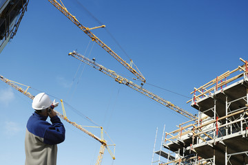 building worker pointing at large construction cranes