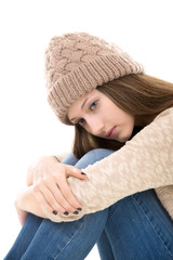 Sad teenage girl sitting embracing her knees
