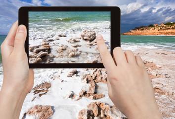 tourist taking photo of salt beach on Dead Sea