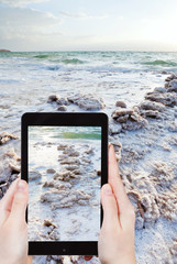 tourist snapping photo of crystal salt on Dead Sea