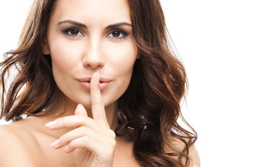 Woman with finger on lips, over white