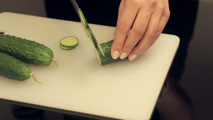 woman cuts cucumber on cutting board
