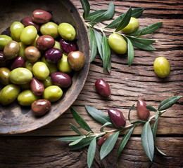 Wooden bowl full of olives and olive twigs besides it. © volff