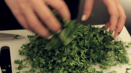 woman shakes greens at the kitchen