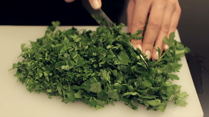 woman cuts fresh parsley