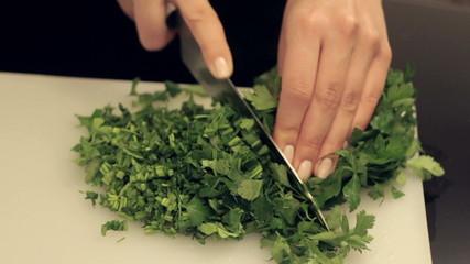 woman cuts fresh greens for salad