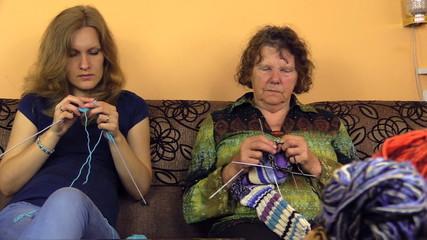 Senior grandma and young granddaughter talk and knit