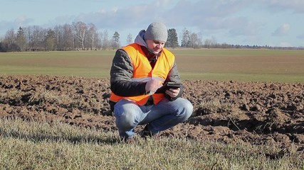 Farmer with tablet PC near plowed field in early spring
