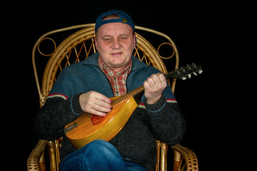 Mature man sitting in wicker chair and playing mandolin