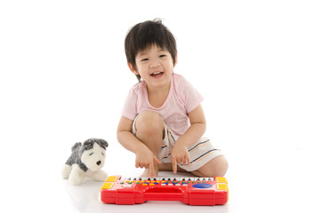 Little asian boy playing electrical toy piano