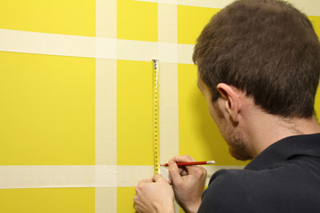 worker man measuring interior wall with masking tape