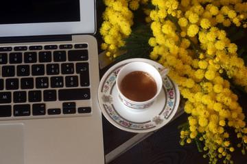 colazione con mimose e tazza di caffè al lavoro