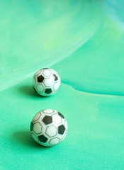 Toy soccer footballs on green canvas background.
