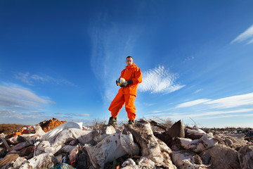 Sanitation worker standing among garbage bags