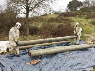 Dos trabajadores de amianto envolviendo tuberías de fibrocemento