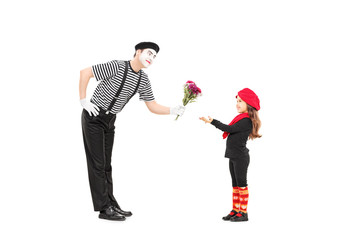 Mime artist giving flowers to a little girl