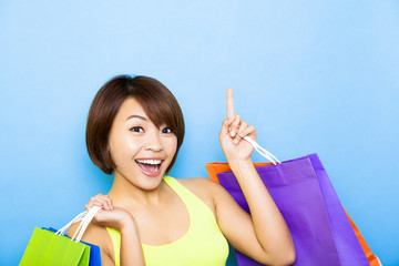 young  woman holding shopping bags and pointing up