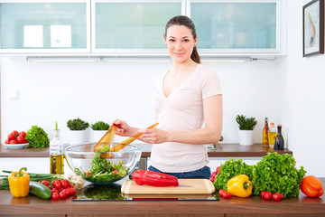 Young woman in the kitchen prepare salad VII