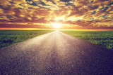 Long straight road, way towards sunset sun