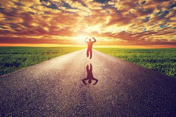 Happy man jumping on long straight road, way towards sunset sun