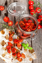 Dried tomatoes and cherry tomatoes on wooden board