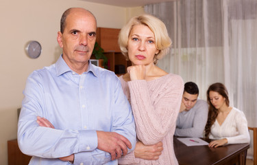 Couple with  bills at table and senior parents apart