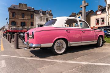 CANCALE, FRANCE - JUNE 23, 2014: Pink vintage car on the coastal