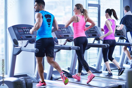 Group of people running on treadmills - 79325260
