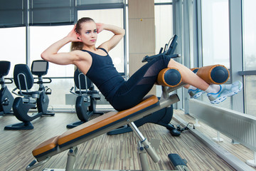 Beautiful woman doing press fitness exercise at sport gym