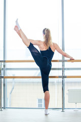 in the hall girl doing stretching near Barre