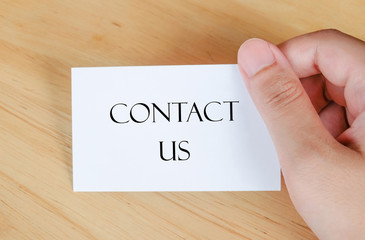 Contact us on paper card in hand, business concept