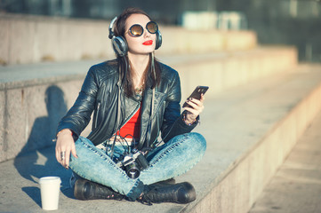 Hipster beautiful girl in leather jacket listening music