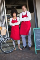 Portrait of happy colleagues in red apron posing